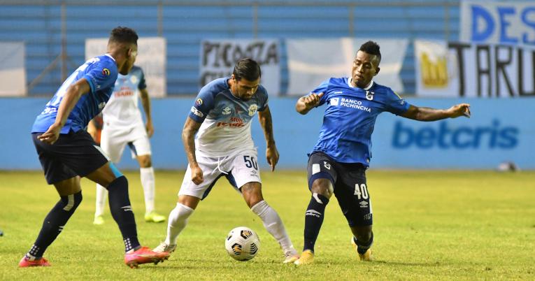 Los jugadores de Católica disputan un balón con Martín Alaniz, del Manta.