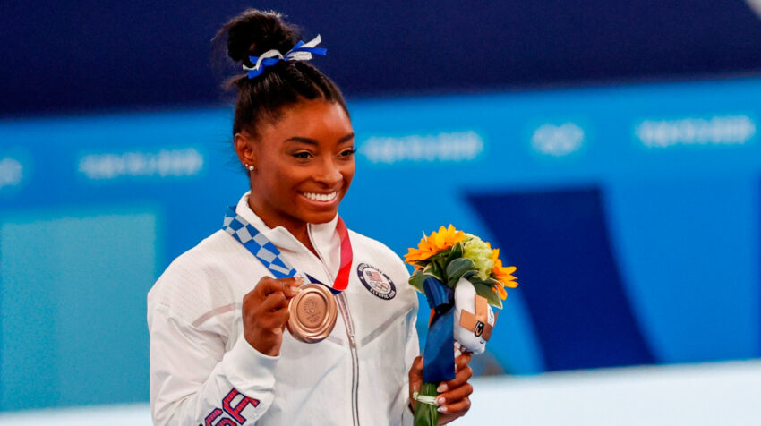 La estadounidense Simone Biles celebra en el podio tras conseguir la medalla de bronce en la final de barra de equilibrio femenina de Gimnasia Artística, el martes 3 de agosto de 2021.