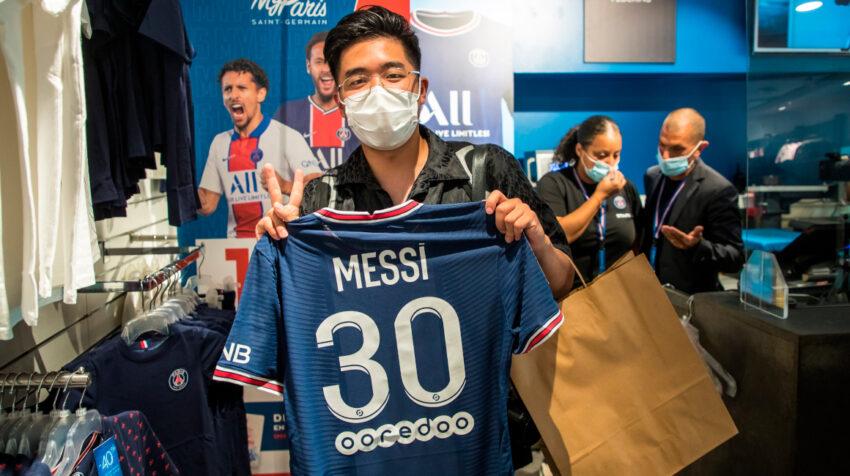 Un aficionado posa con la camiseta de Messi dentro de la tienda del PSG.