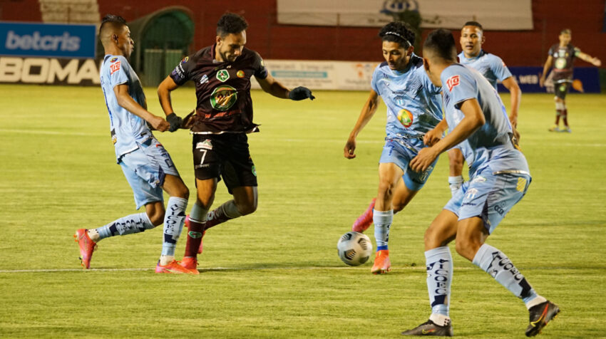 Tres jugadores de Macará intentan adueñarse de la pelota en el partido ante Mushuc Runa por la LigaPro, en Ambato, el 20 de agosto de 2021.