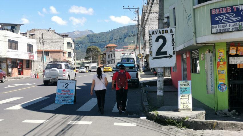 Dos personas caminan en medio de letreros que ofrecen lavado de autos, el 3 de septiembre de 2021.