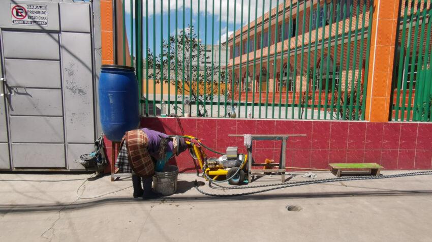 Una mujer instala una lavadora de autos improvisada sobre la calle Cusubamba, en el sur de Quito, el 3 de septiembre de 2021.