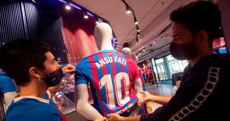 Empleados del Barça Store Camp Nou colocan la nueva camiseta del delantero del Barcelona, Ansu Fati, en un maniquí.