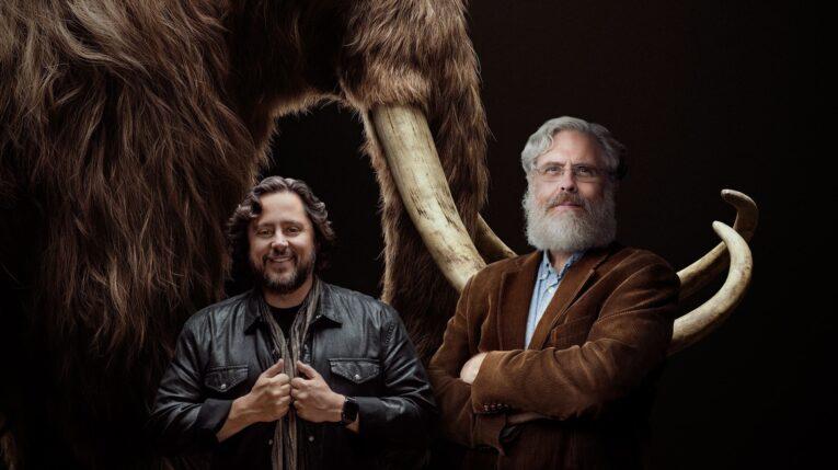 Fotografía cedida por la empresa Colossal donde aparecen sus cofundadores, los empresarios y científicos Ben Lamm (i) y George Church (d), mientras posan frente a la imagen de un mamut.