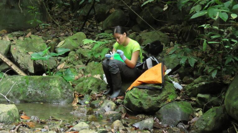 Investigadora tomando muestras de un río amazónico.