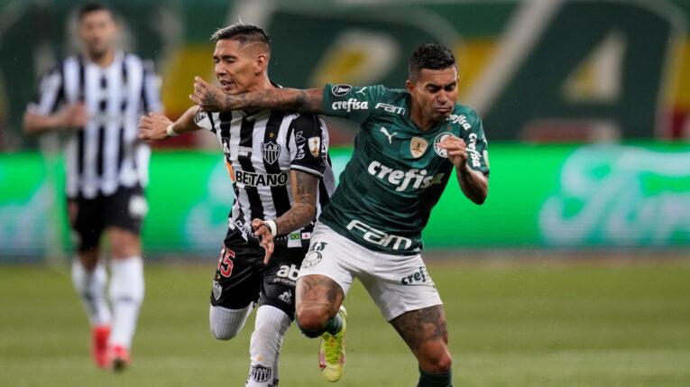 Eduardo Pereira (d) de Palmeiras disputa un balón con Matías Zaracho de Mineiro, en la semifinal de ida de la Copa, el 21 de septiembre de 2021, en Brasil.